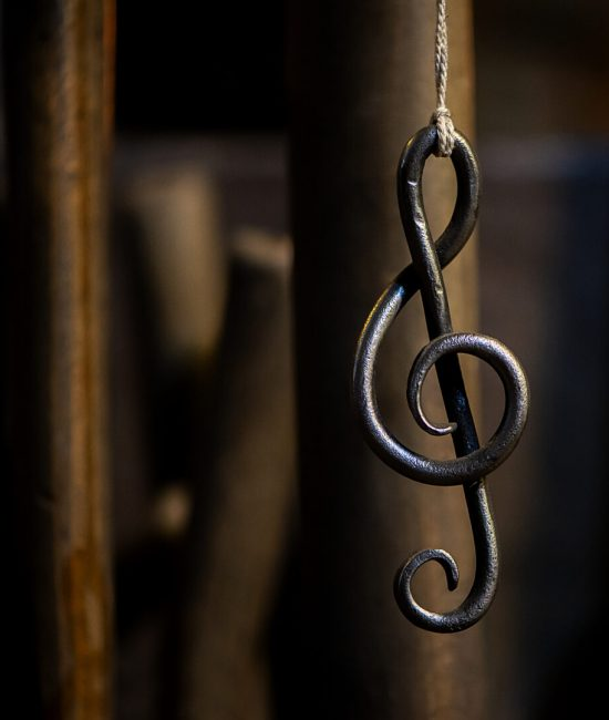 a metal sheet music key hangs in a rope in a blacksmith's workshop